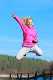 Cheerful woman teenage girl in tracksuit jumping showing outdoor. Full length of cheerful woman teenage girl in pink tracksuit jumping high showing pointing at Royalty Free Stock Image
