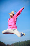 Cheerful woman teenage girl in tracksuit jumping showing outdoor. Full length of cheerful woman teenage girl in pink tracksuit jumping high showing pointing at Royalty Free Stock Photos
