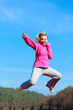 Cheerful woman teenage girl in tracksuit jumping showing outdoor. Full length of cheerful woman teenage girl in pink tracksuit jumping high showing pointing at Royalty Free Stock Photo