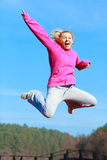 Cheerful woman teenage girl in tracksuit jumping showing outdoor. Full length of cheerful woman teenage girl in pink tracksuit jumping high showing pointing at Royalty Free Stock Photography