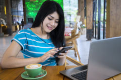 Cheerful woman texting in the cafe Stock Images