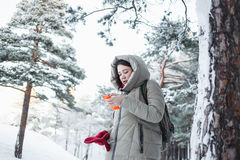 Cheerful woman texting on orange smartphone during a trip to the forest in winter Brunette model wearing warm  jacke Royalty Free Stock Image