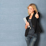 Cheerful woman with thumb up. Beautiful woman leaning on wall with touchpad Stock Photo