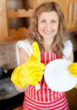 Cheerful woman with thumb up drying dish Royalty Free Stock Images