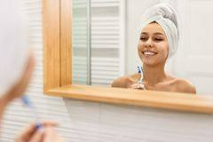 Cheerful woman with toothbrush near mirror royalty free stock image