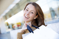 Cheerful woman in town with shopping bags Stock Photo