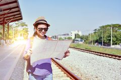 Cheerful woman traveler holding location map in hands. While looking for some direction in Thailand scene in sunny summer day royalty free stock images