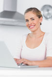 Cheerful woman typing on laptop Stock Photo