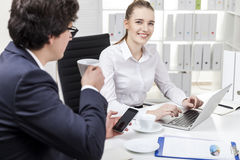 Cheerful woman is typing in office while her colleague is drinki Royalty Free Stock Photo