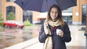 Cheerful woman under umbrella drinking coffee. Cheerful attractive young woman wearing a gray coat is standing under an umbrella and drinking coffee. Handheld stock footage