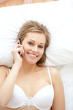 Cheerful woman in underwear talking on phone Royalty Free Stock Images