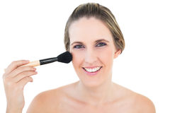 Cheerful woman using blusher brush Stock Photography