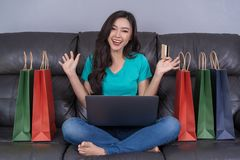 cheerful woman using digital tablet for online shopping with credit card in living room royalty free stock photos