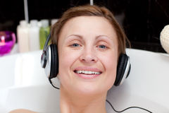 Cheerful woman using headphones in a bubble bath Royalty Free Stock Photos