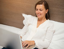 Cheerful woman using her laptop in the bedroom Royalty Free Stock Photos