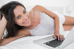 Cheerful woman using her laptop lying in bed Royalty Free Stock Image
