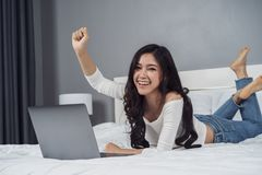 Cheerful woman using laptop computer on bed Stock Image
