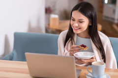 Cheerful woman using laptop and eating cake in a cafe. Work and pleasure. Beautiful charming joyful woman relaxing and having cake while using her laptop in a Stock Photos