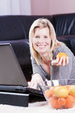 Cheerful woman using a laptop at home. Royalty Free Stock Image
