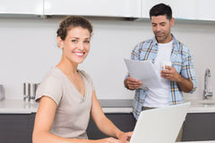 Cheerful woman using laptop while partner reads the newspaper Royalty Free Stock Image