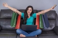 Cheerful woman using laptop to successful shopping online with c stock images