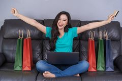 Cheerful woman using laptop to successful shopping online with c royalty free stock photo