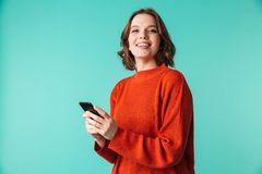 Cheerful woman using mobile phone. Photo of cheerful woman standing isolated over blue background looking camera using mobile phone Stock Photography