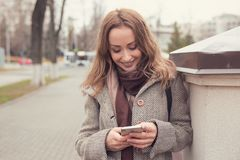 Free Cheerful Woman Using Phone Outdoors Royalty Free Stock Images - 129593199