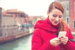 Cheerful woman using phone on street. Young redhead woman in warm pink coat using smartphone while standing on street stock photography