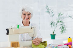 Cheerful woman using the sewing machine at home Royalty Free Stock Photo