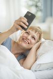 Cheerful Woman Using Smart Phone In Bed Stock Photography