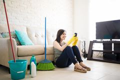 Cheerful woman using smartphone. Cute woman using mobile phone sitting on a cleaned floor in living room Royalty Free Stock Images