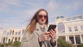 Cheerful woman is viewing photos and reading sms in mobile phone outdoors stock video