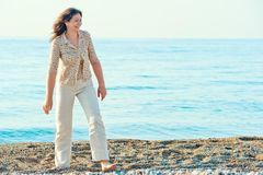 Cheerful woman walking along the beach Stock Images