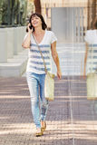 Cheerful woman walking on sidewalk with smart phone Royalty Free Stock Photo