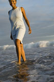 Cheerful Woman Walking Through Surf On Beach Stock Photography