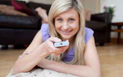 Cheerful woman watching TV lying on the floor Stock Image