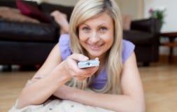 Cheerful woman watching TV lying on the floor Stock Image