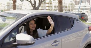 Cheerful woman waving out of car. Beautiful young woman sitting inside of modern car and waving with hand greeting someone in sunny day at street Stock Photo