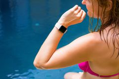 Woman wearing digital watch on hand by the pool royalty free stock photography