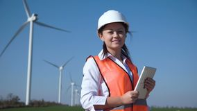 Smiling female engineer standing against wind farm. Cheerful woman wearing hard hat standing against turbines at wind farm on sunny day