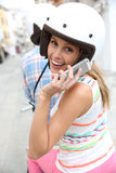 Cheerful woman wearing helmet talking on the phone Royalty Free Stock Photos