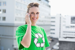 Cheerful woman wearing recycling tshirt having a call Royalty Free Stock Photography