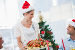 Cheerful woman wearing santa hat and bringing a roast chicken Royalty Free Stock Image