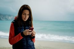 Cheerful woman wearing a sports vest texting on smartphone during a trip to the beach on winter or autumn. royalty free stock photo