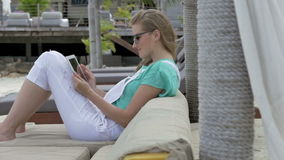Cheerful woman wearing sunglasses sitting in hotel lounger using digital tablet during vacation. Young blonde woman reading e-book in tropical resort. Woman stock footage