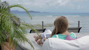 Cheerful woman wearing sunglasses sitting in hotel lounger using digital tablet during vacation. Young blonde woman reading e-book in tropical resort. Woman stock video