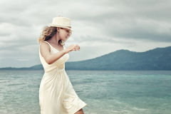 Cheerful woman wearing white dress on a beach on background of t. Pretty girl in a white dress walking on the beach before the rain on a background of dramatic royalty free stock image