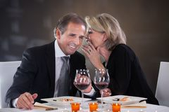 Cheerful woman whispering in man's ear Stock Photo