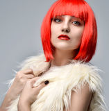 Cheerful woman in white fake fur coat in hot red party wig. Close up funny fashion portrait of cheerful woman in white fake fur coat in hot red party wig on a Royalty Free Stock Photo